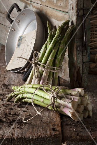 A rustic arrangement featuring two bunches of green asparagus