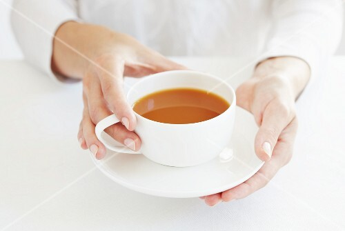 A woman holding a cup of redbush tea with milk