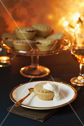 Mince pies on a cake stand, with one on a plate with cream (Christmas)