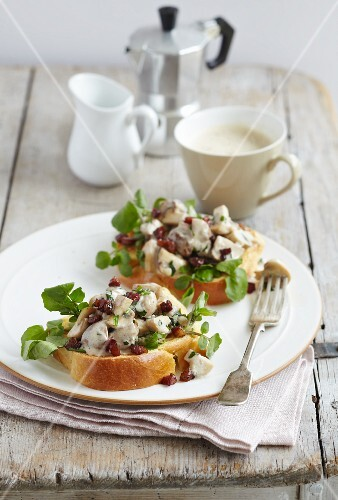Two slices of brioche toast topped with mushrooms, tarragon and watercress