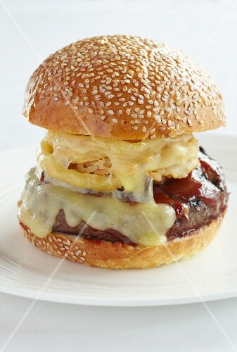 A beefburger with onion rings, melted cheese and barbeque sauce