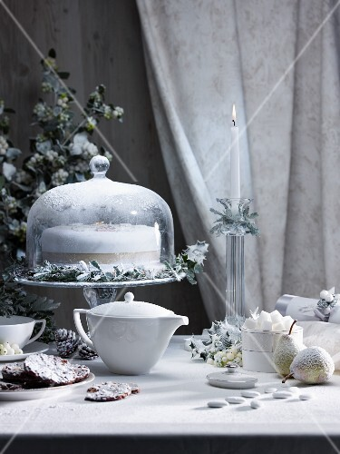 A Christmas table laid with cake, florentines, sugared almonds and tea