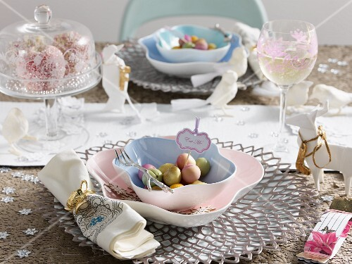 A table laid for Christmas with a paste-coloured place mats, crystal glasses and decorative animal figurines