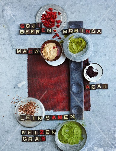 Still-life arrangement of goji berries, moringa, acai, maca, wheatgrass and flaxseed
