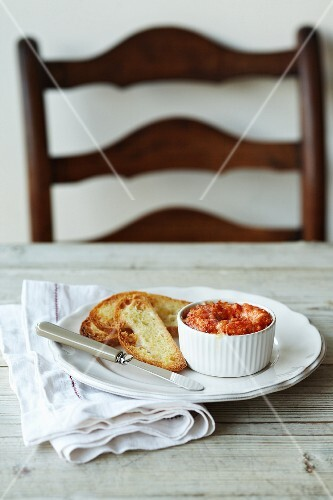 A crab pie with melted cheese served with grilled bread