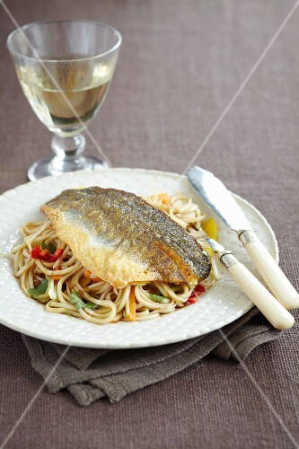 Fish fillets on egg noodles with chilli peppers and coriander