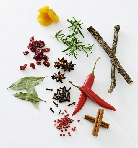 Spices, herbs and dried fruit on a white surface