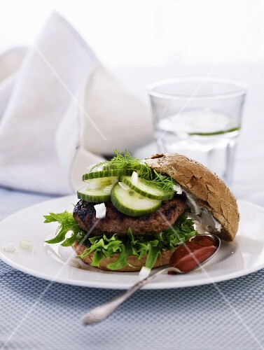 A hamburger with gherkins and ketchup