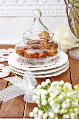 Sweets in glass jar with lid and bouquet of lily-of-the-valley in foreground