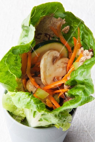 A vegan lettuce wrap with vegetables and sunflower seed cream