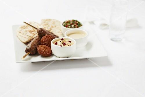 Kofta and falafel with pita bread, hummus and tomato salad