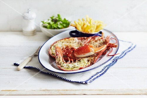 A halved lobster with chips and a side salad