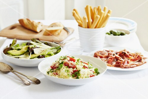 A Mediterranean buffet with Parma ham, an avocado and fennel salad, olives and vegetable couscous served with bread