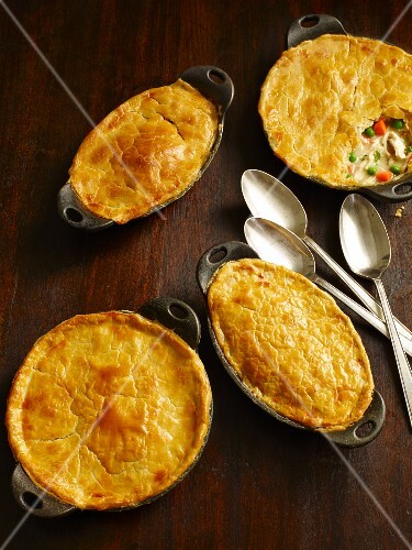 Chicken pot pies in baking dishes on a wooden table with spoons