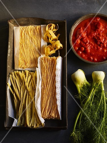 Dried pasta on a baking tray with tomato sauce and fresh fennel