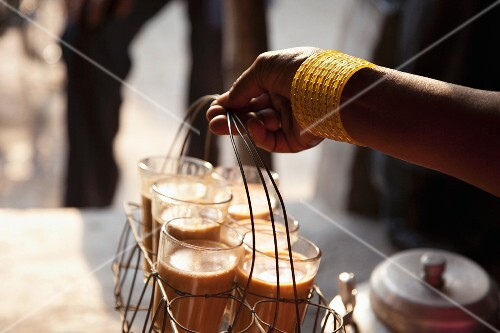 A woman's hand holding a basket of freshly made morning chai
