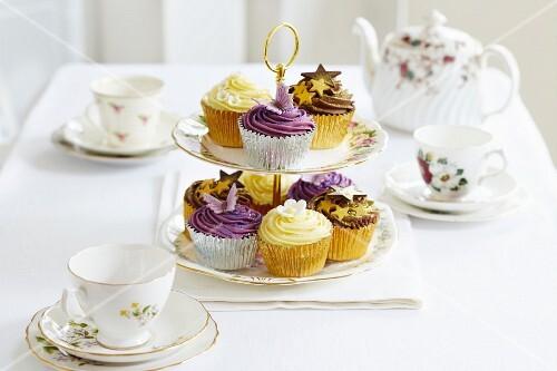 Various cupcakes on a cake stand between tea crockery
