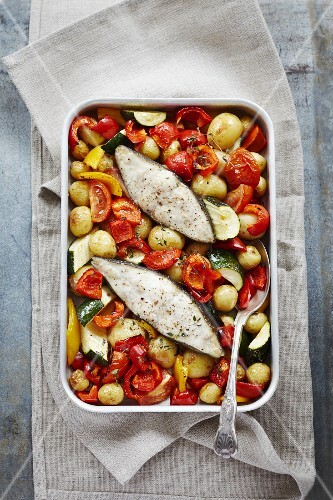 Baked fish with tomatoes, red and yellow peppers and courgettes