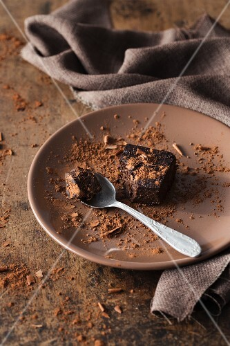 A brownie on a brown plate with a bite taken out of it