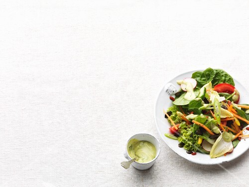 A mixed leaf salad with vegetables and a dressing
