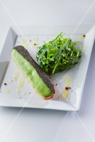 An éclair with salmon cream, wasabi glaze and poppy seeds served with rocket