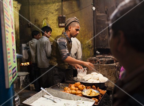 Traditional street food (unleavened rice bread and fried aloo tikki potatoes) at a street stall in Varanasi, India