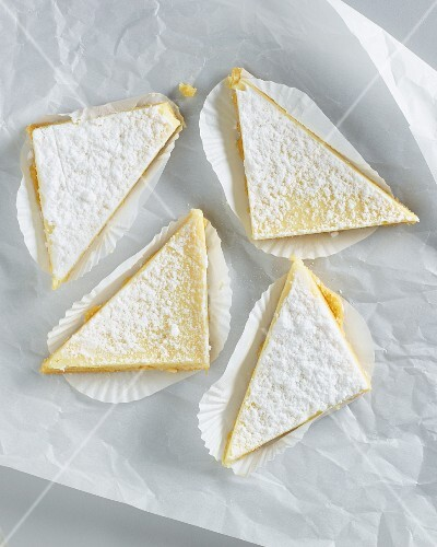 Lemon tart triangles with icing sugar on white parchment paper