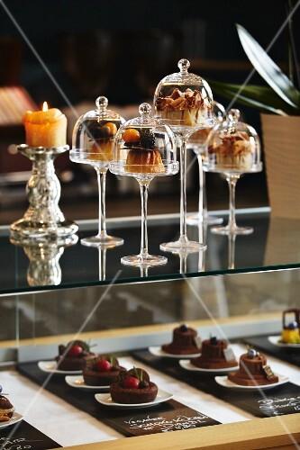 Desserts under mini glass cloches on a bar in a restaurant