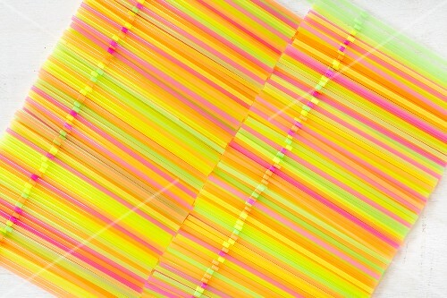 Two rows of colourful drinking straws (seen from above)