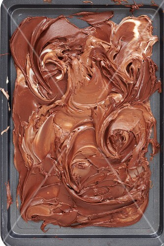 Melted milk and dark chocolate mixed together on a baking tray