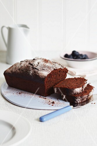 A chocolate loaf cake dusted with icing sugar with a bowl of blueberries in the background