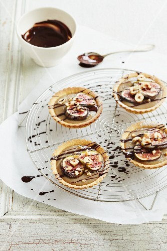 Four caramel tartlets with figs and drizzled chocolate