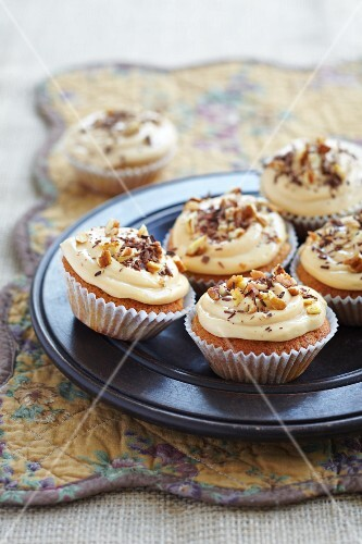 Fairy cakes decorated with frosting, walnuts and chocolate curls