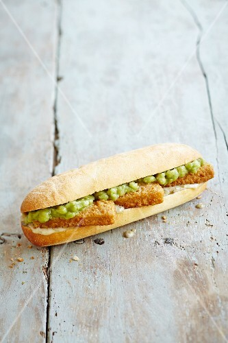 A sub sandwich with fish fingers, tartare sauce and mushy peas