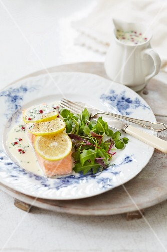 Poached salmon fillet with a pink pepper sauce, lemons and salad