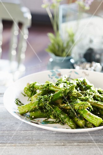 Cooked asparagus with steamed rocket and sesame seeds