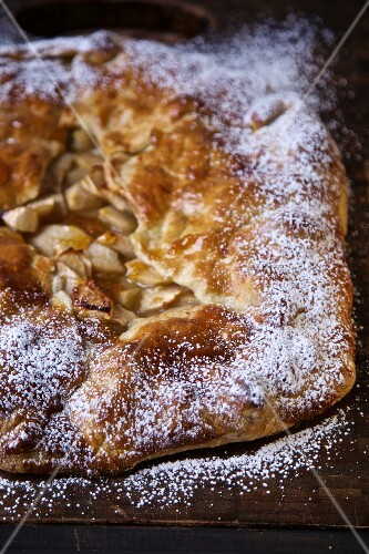Apple tart with icing sugar on a chopping board
