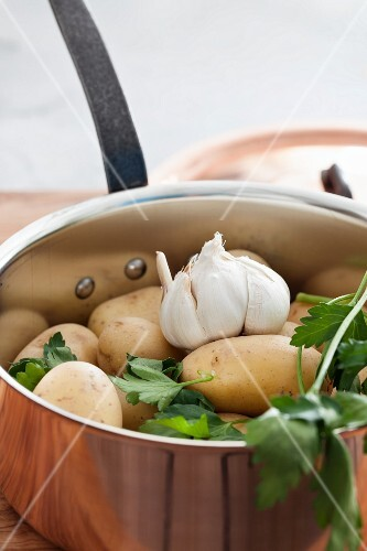 Potatoes, garlic and parsley in a copper pan