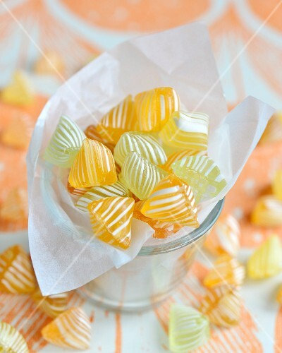 Yellow and white striped bonbons in a glass