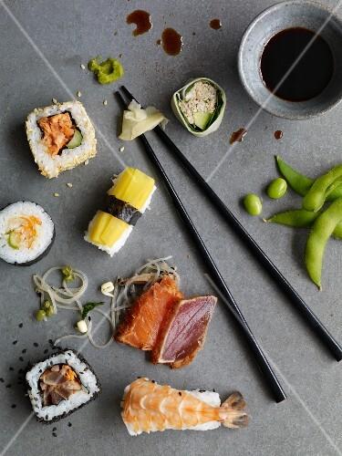 Nigiri sushi, California rolls, maki sushi and sashimi on a grey surface