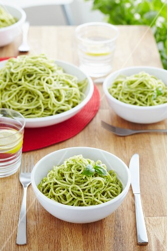 Spaghetti with basil pesto on a dining table
