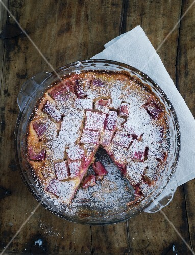 Rhubarb cake in a baking tin on a wooden table
