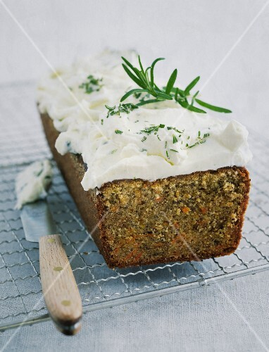 Carrot cake with cream cheese frosting on a wire rack with a palette knife
