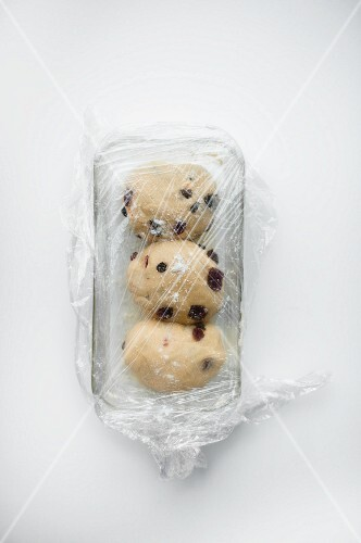 Unbaked fruit loaf in a baking dish, covered with clingfilm