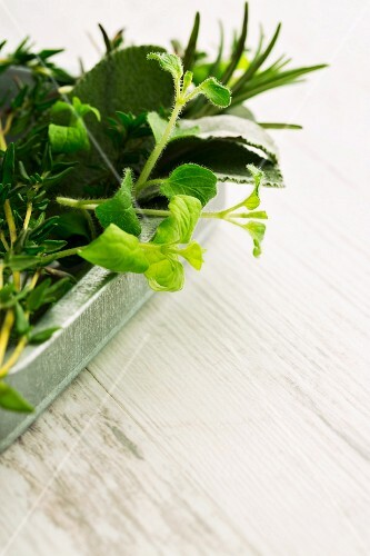 Herbs de Provence in a metal dish on a wooden surface