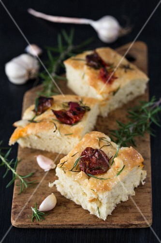 Pieces of focaccia with dried tomatoes, garlic, rosemary and olive oil