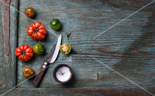 Green and red tomatoes with salt and a knife