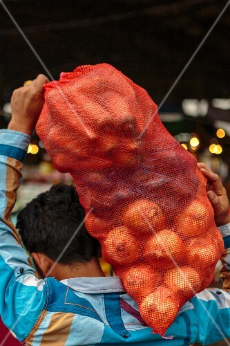 A man carrying a sack of onions at a market (Vientiane, Laos)