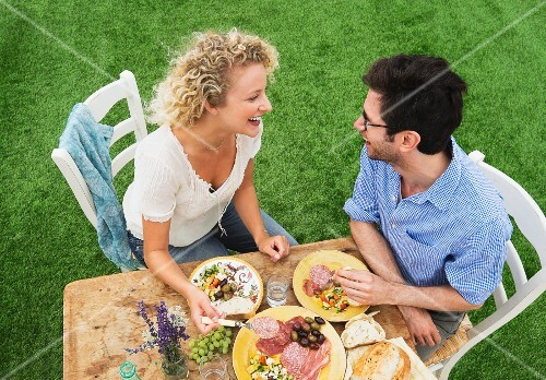 A couple eating a rustic breakfast in a garden