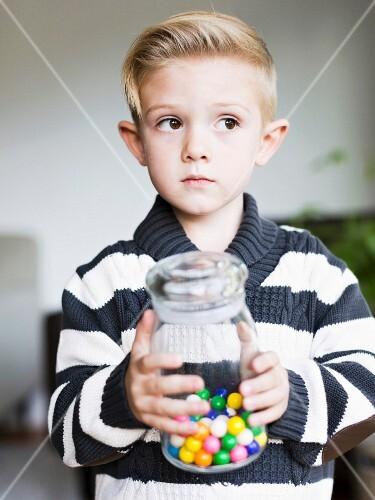 A boy holding a jar of bonbons
